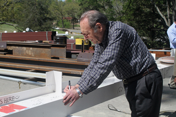Veteran writer Jim Bailey signs the final beam at WMS.